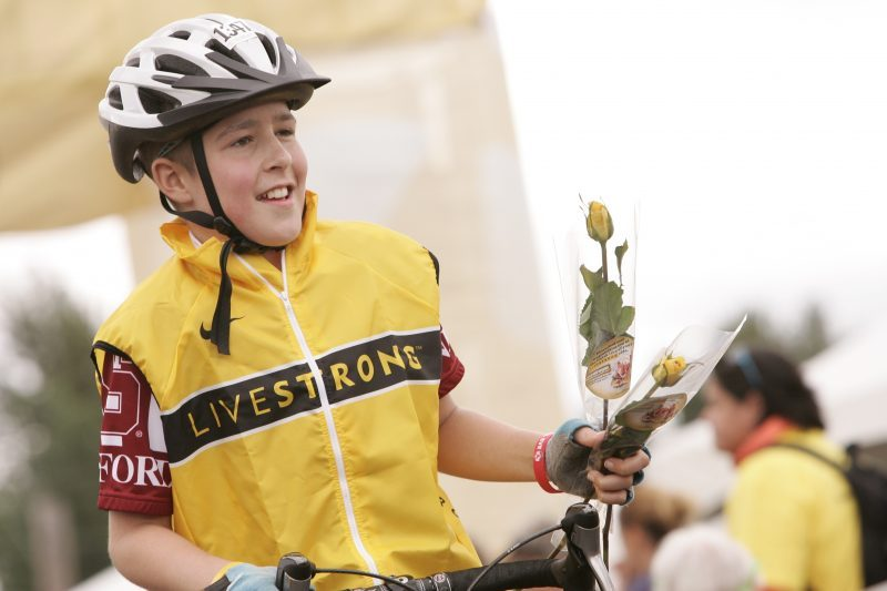 an image of Jimmy in a cycling outfit and cycling helmet holding a rose after he completed a cycling race
