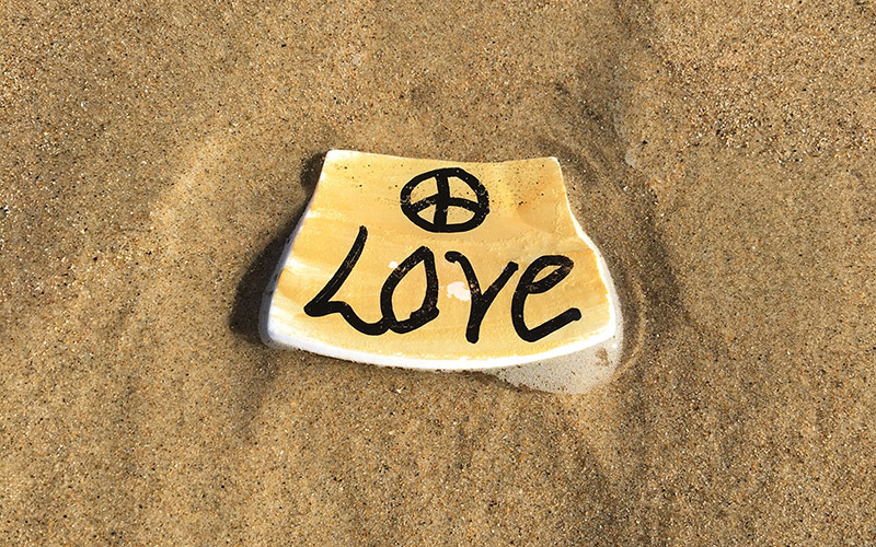 an image of a piece of broken pottery embedded in the sand on a wet beach with the word 'Love' on it and a peace sign above the word