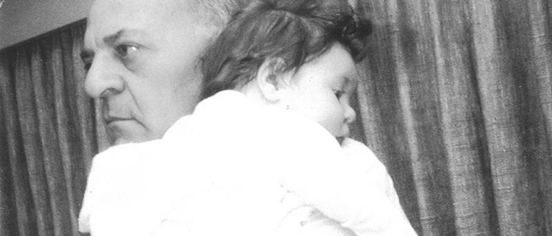 an old black and white image of Margo as a baby being held by her father as she rests her head on his shoulder