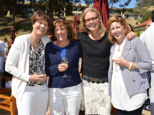 an image of Margo standing with 3 of her female friends on a sunny day, all holding wine glasses at an outdoor event