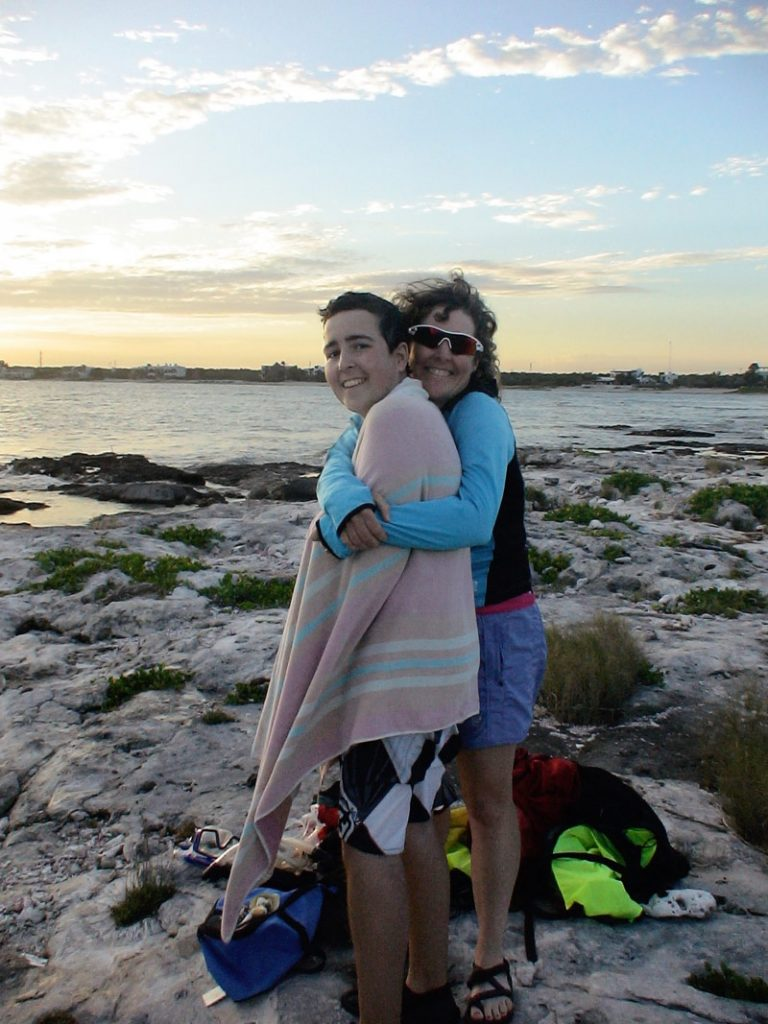 an image of Margo hugging Jimmy, who is wrapped in a towel, standing on a rocky beach at sunset