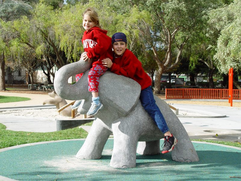 A photo of Jimmy and Molly sitting/playing on a stone elephant at the neighborhood park