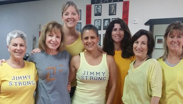 an image of a group of ladies in workout clothing posing together for a photograph inside of a gymnasium