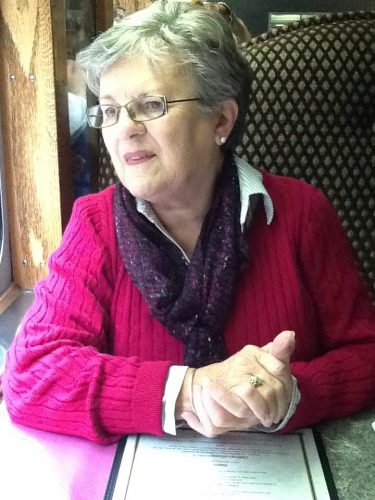 The author's mother seated wearing a pink sweater and purple scarf