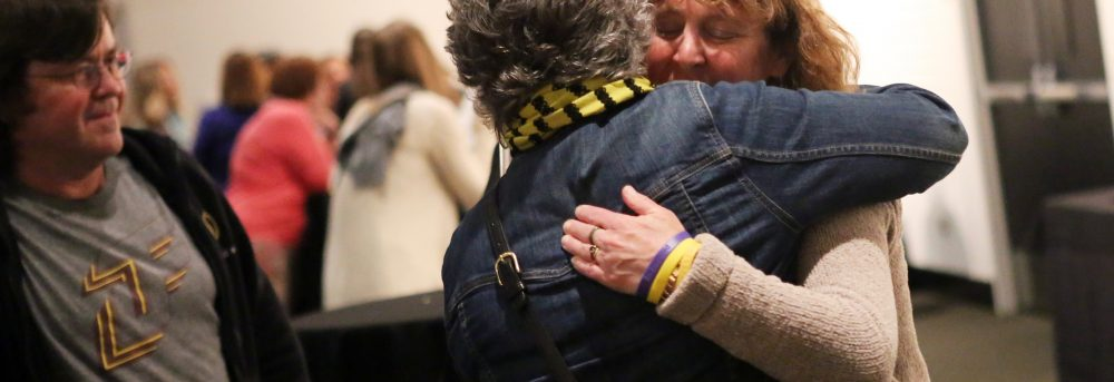 Margo hugging a friend (only the friend's back is showing) at Jimmy's celebration of life; Margo's friend Jerry is on the left wearing a JimmySTRONG shirt