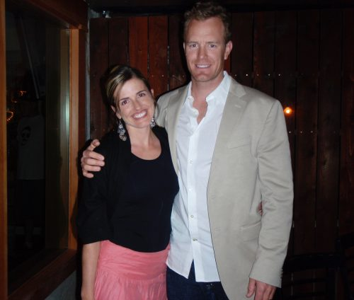 Image of Jen and Matt at a surprise party. Jen is wearing a black top and salmon colored skirt; Matt is wearing a beige suit jacket and white shirt. They have one arm around the other.