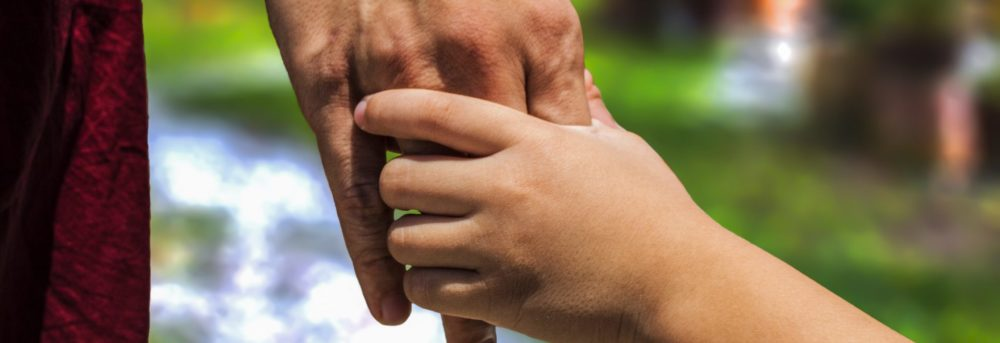 Photo with blurry background of a parent and child holding hands. Only the hands and part of the wrists are in the photo.