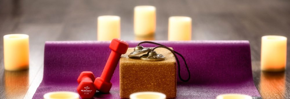 Photos of a yoga mat rolled with a yoga block and light weights on it surrounded by candles