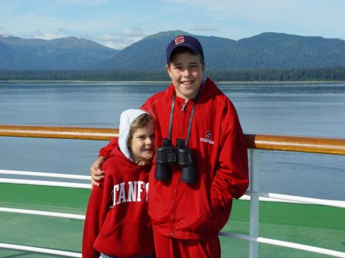 Molly and Jimmy standing next to each other on the deck of a cruise ship in Alaska. They're both wearing Stanford University jackets.