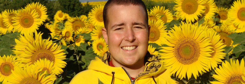 Jimmy standing in a field of sunflowers; only his head and shoulders are visible