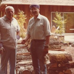 Dad and Seymour at Fernrock standing in front of a stack of wood