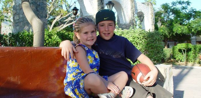 Molly and Jimmy sitting next to each other on a bench in Cabo San Lucas, Mexico. Molly has corn rows and is wearing a blue and yellow flowered dress. Jimmy is holding a football and has his right arm around Molly. He's wearing a blue t-shirt and khaki shorts