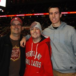 Dan, Jimmy and Willie at the Portland Trail Blazers. Dan is on the left wearing a Stanford baseball hat and black jacket; Jimmy in the middle wearing a Portland Trailblazers hoodie and beanie; Willie on the right wearing a gray sweatshirt with his arm around Jimmy