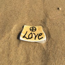 Small piece of yellow broken pottery with a peace sign above the word LOVE sitting on the sand at Pismo Beach