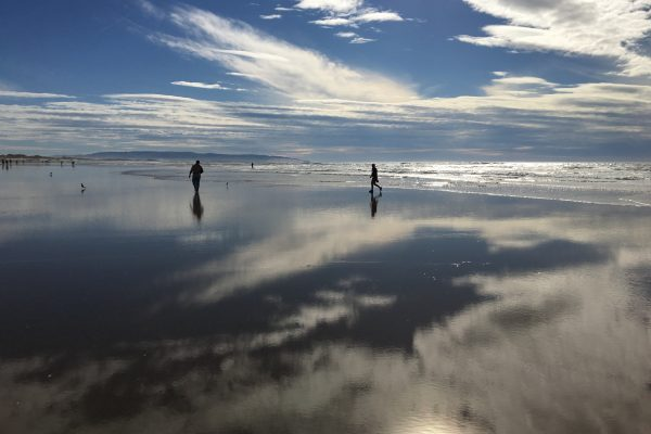 Two images in the distance on the wet sand at the beach. The sky is reflected on the water.