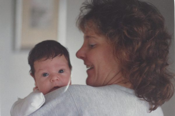 Margo holding Jimmy age 1 month. Margo is looking at Jimmy on her left shoulder; Jimmy is looking at the camer