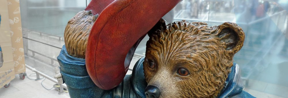 Photo of upper half of Paddington the Bear statue. Paddington is wearing a blue jacket and tipping his red hat.