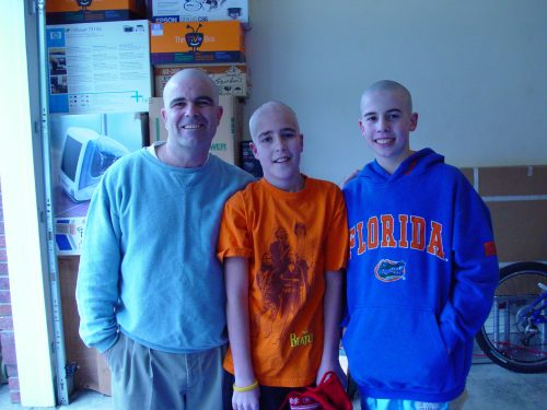 Dan, Jimmy and Willie with bald heads at Jimmy's head shaving party. Dan is wearing a blue pullover, Jimmy is wearing an orange shirt, Willie is wearing a Florida Gators sweatshirt