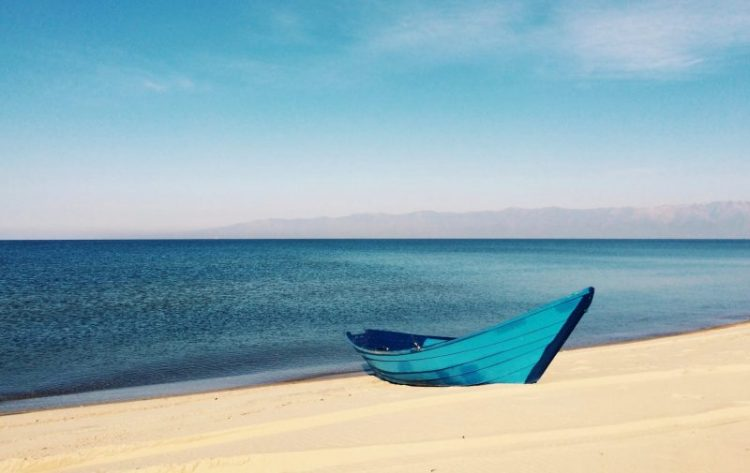 Turquoise rowboat on sand with ocean and blue sky in the background