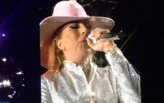 Lady Gaga on stage wearing a white jacket and a pink hat with the microphone in her left hand close to her face