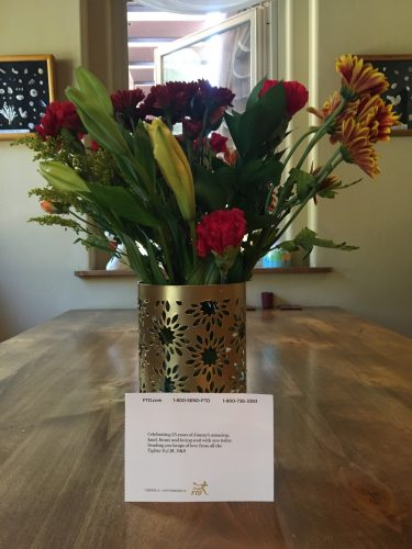 Floral arrangement with mostly red flowers, roses and carnations, in a gold vase with a card in front.