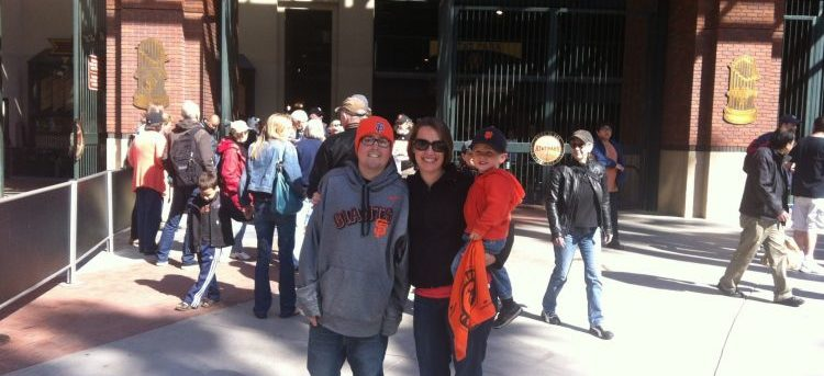 Jimmy, Shannon and Theo at AT&T Park. Jimmy is wearing an orange SF Giants cap, a gray Giants' sweatshirt and blue jeans. Shannon is wearing sunglasses, a dark shirt and dark pants. Theo is wearing a Giants' cap, an orange Giants' sweatshirt and carrying an orange Giants towel
