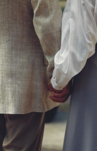 Mom and Dad holding hands at Margo's wedding. Dad is wearing a beige sports coat; Mom is wearing a white blouse and purple skirt. Only their hands and forearms and part of their sides are visible.