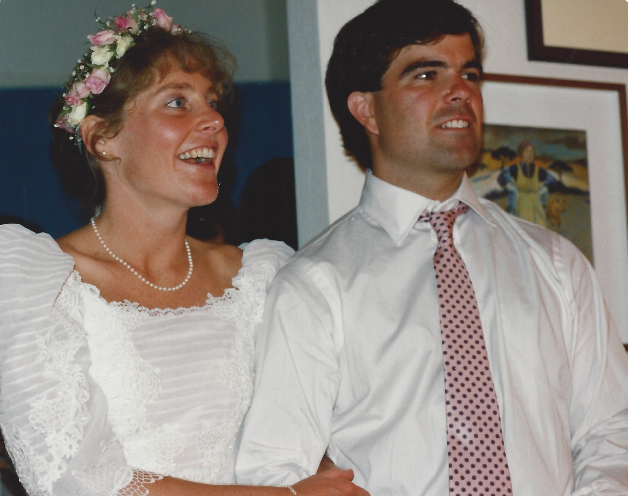 Dan and Margo on their wedding day. Margo is on the left wearing a white gown with pink roses and white flowers in her hair; Dan is wearing a white shirt and pink tie.