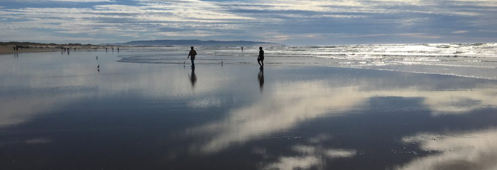 Distant sillouettes of Molly and Dan on Pismo Beach. The clouds are reflecting on the wet sand