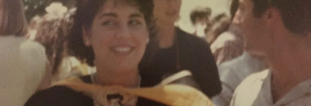 The author, Pia Spector on graduation day wearing her black robe with a white dress underneath. Her now deceased then boyfriend is shown in profile on the right