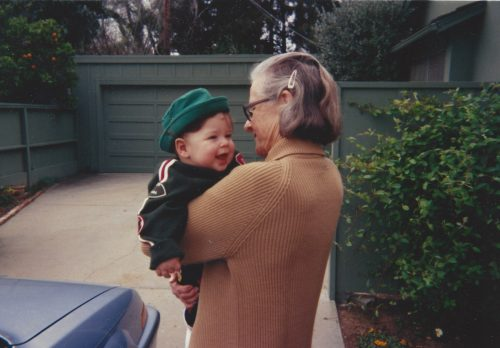 Mom holding Jimmy age 18 months. Mom is wearing glasses and a tan sweater; her gray hair is held back by a clip. Jimmy is wearing a green jacket and green hat.