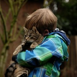 Photo of boy holding cat. The cat's face is in front of the boy's. The boy has reddish colored hair and a blue and green checked jacket.