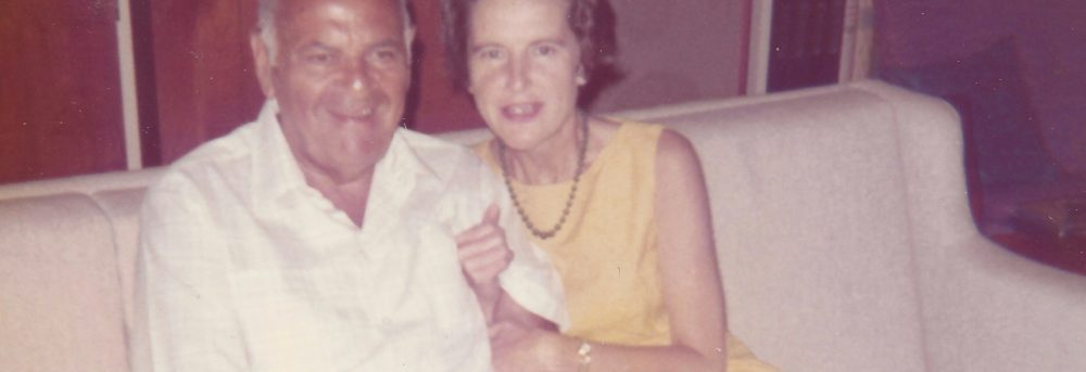 Dad is seated wearing a white shirt; Mom is sitting next to him with her hands around his arm.