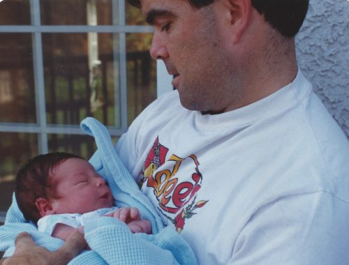 Dan holding Jimmy, age four days. Dan is wearing a white t-shirt and looking down at Jimmy who is wrapped in a blue blanket