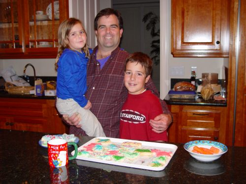 Dan holding Molly, age 5 and with his arm around Jimmy, age 10 standing in front of a tray of decorated Christmas cookies.