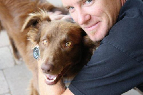 Bear, a chocolate brown lab, and Matt Klee, the author's husband. They are both looking at the camera. Matt is wearing a navy t-shirt.