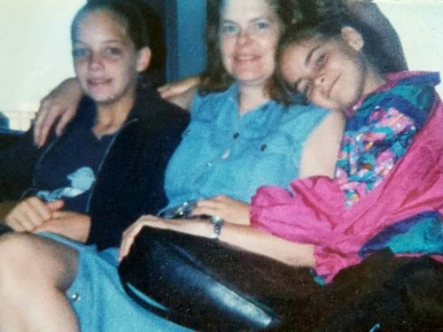 Sarah, Bernie and Jessica sitting on a couch. Sarah is wearing a black jacket and navy t-shirt; Bernie has her arm around Sarah and is wearing a sleeveless jean dress; Jessica is wearing a pink print shirt and has her right arm around Bernie and her head on Bernie's shoulder