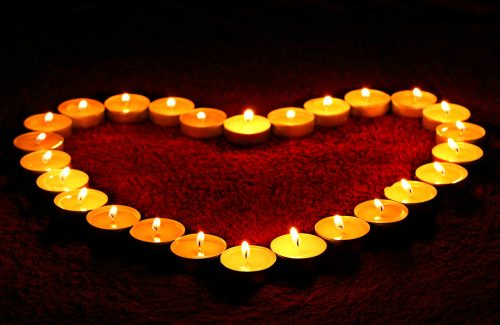 Yellow and orange candles burning in the shape of heart. The heart is red inside.