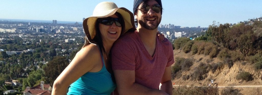 Ana wearing a teal tank top and straw hat; Daniel wearing a salmon shirt and sunglasses