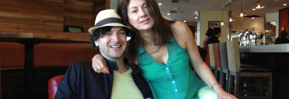 Daniel Velez, sitting in a chair wearing a black shirt and white straw hat with black band; Ana Velez sitting on his lap wearing a green shirt