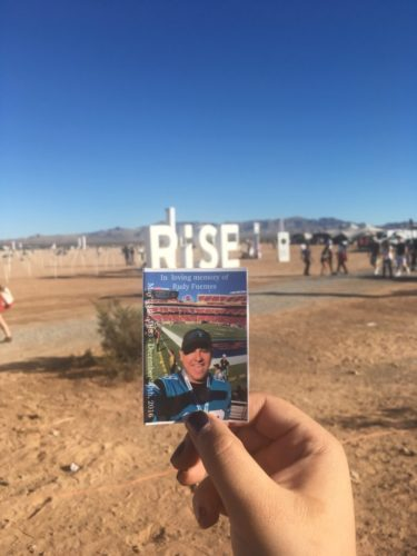"""Alyssa holding a photo of Rudy with the caption at the top that says """"In loving memory of Rudy Fuentes"""". The word RISE can be seen in the background."""