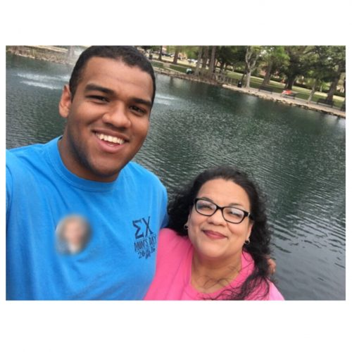 Brandon and Sarah Cavazos. Brandon is wearing a bright blue t-shirt with a fraternity campaign button on his right chest. Sarah is on the right wearing a pink shirt. They are standing in front of a pond.
