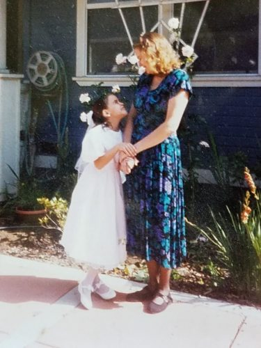 Jessica in a white flower girl type of dress with white shoes holding Bernie's hands and looking up at her; Bernie is wearing a blue print dress and is looking down at Jessica