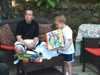 Jimmy sitting on the couch wearing a black t-shirt and white shorts. Gage is standing to his left wearing a white shirt and blue and white shorts, opening a present