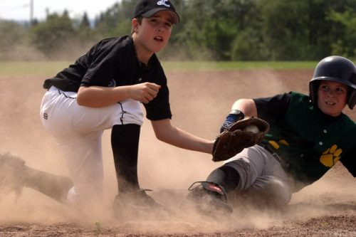 Jimmy wearing a black baseball top and white baseball pants and a black baseball hat with a script L on it making a tag at third base as the running slides in