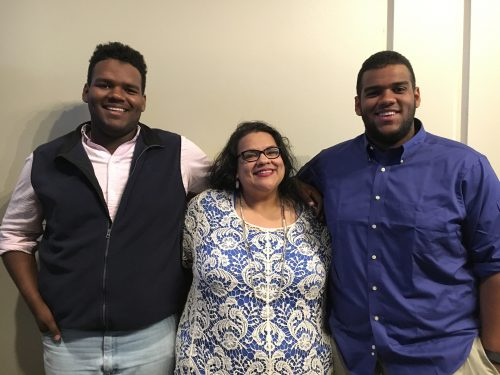 Blaine, Sarah and Brandon Cavazos. Blaine is wearing a white shirt and dark brown sweater vest. Sarah is wearing a blue and white print dress and black glasses. She is in the middle. Brandon is on the right and he is wearing a dark blue button down shirt.