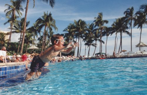 Jimmy age four jumping into a pool at the Hyatt Maui. He's wearing blue swim trucks and goggles