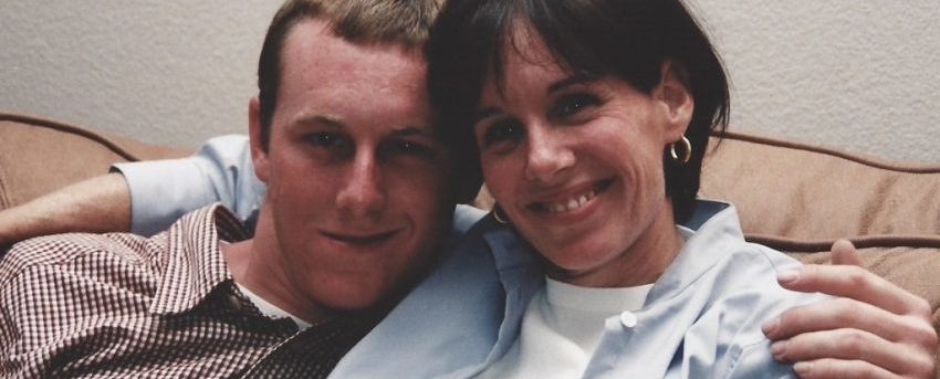 Sean and his mom, Lise, sitting on a couch. Sean is on the left wearing a brown checked shirt; Lise is on the right wearing a white shirt with a blue button down shirt over it and she has her arm around Sean