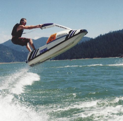 Sean standing on a jet ski, in the air over the water