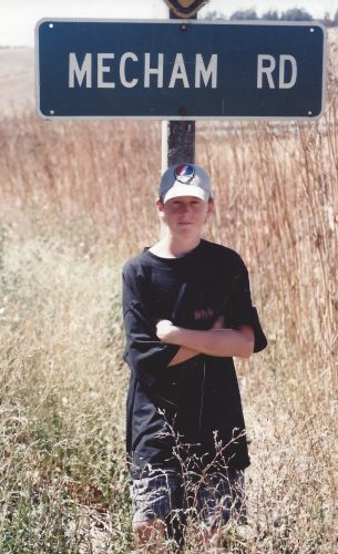 "Sean is leaning against a sign that says ""Mecham Road"". He's wearing a baseball cap, black shirt and black shorts. His arms are crossed."